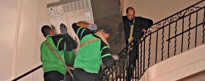 Portage de lave vaisselle à bras d'homme dans un escalier