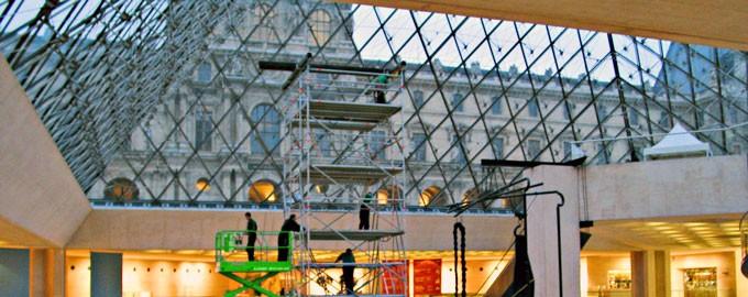 Montaje de una obra de arte contemporáneo sobre la pirámide del Louvre